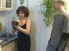 Russian mom plus youthful gentleman playing far kitchen